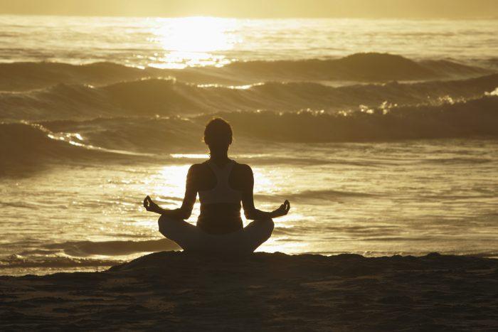 Woman meditating on beach at sunrise